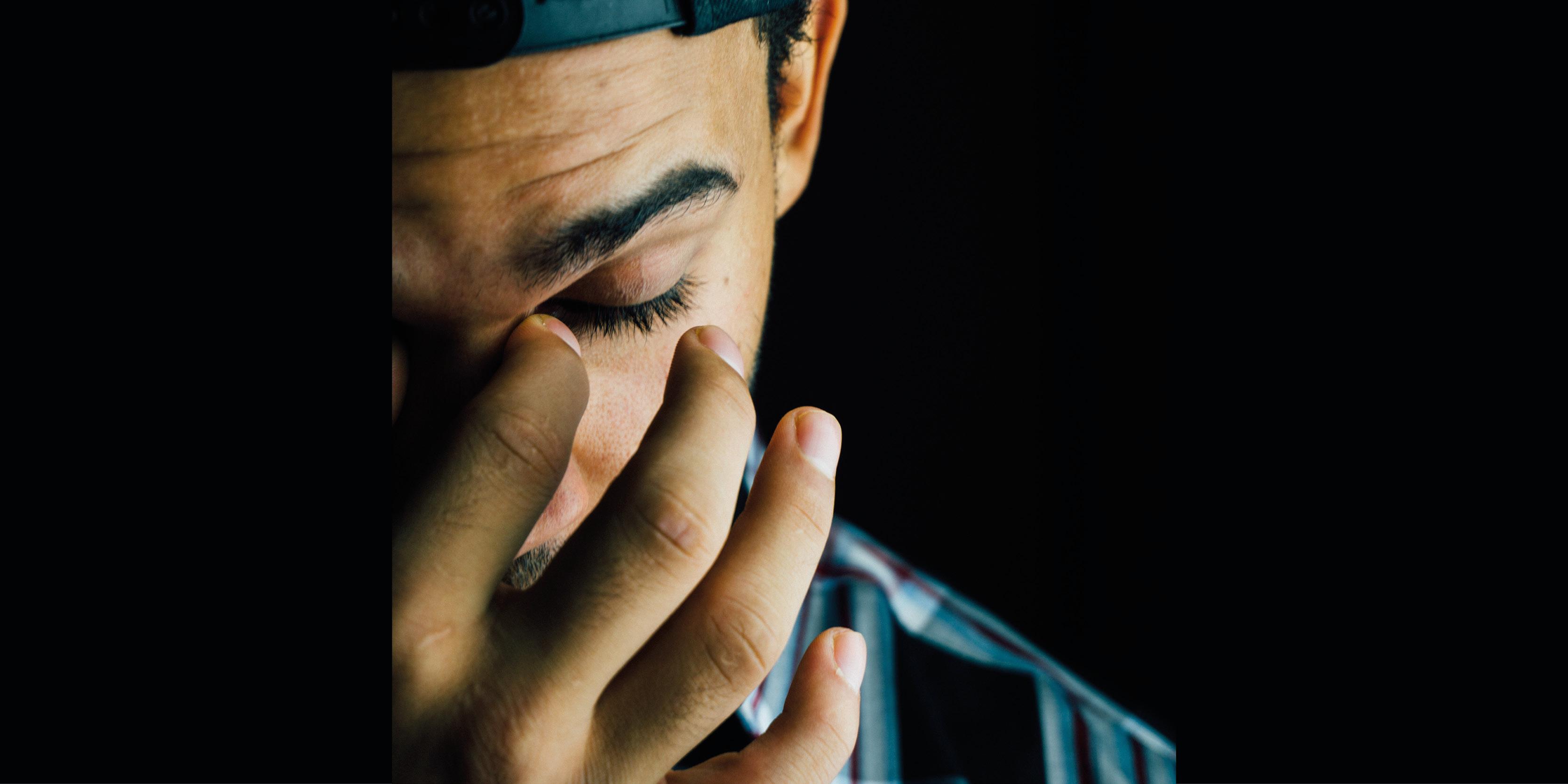 Fatigue - Müdigkeit, Mann reibt sich müde die Augen Chronisches Fatigue-Syndrom nach einer Covid-19-Erkrankung kann die Aktivitäten des täglichen Lebens beeinflussen.