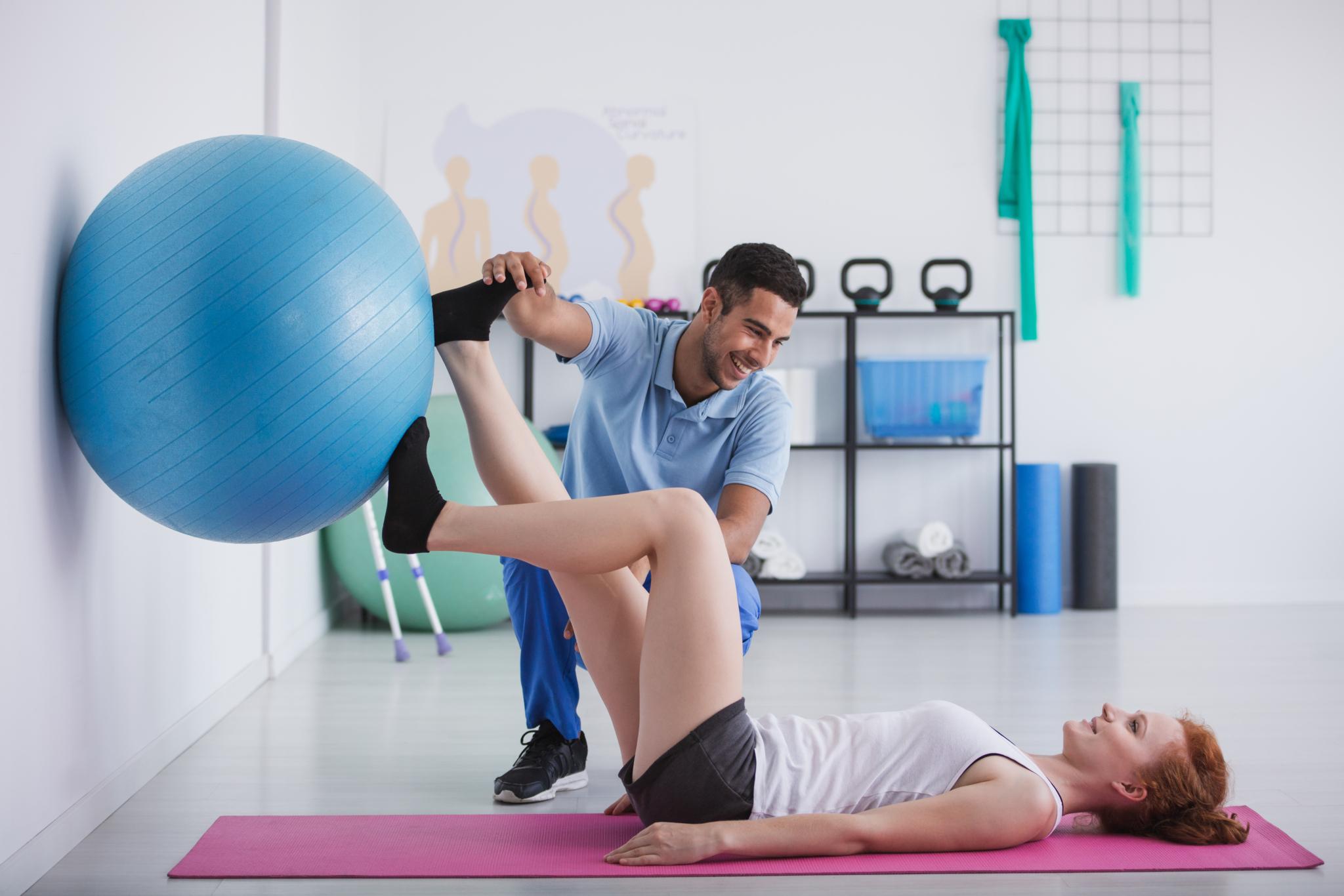 Physiotherapeut, der einer Patientin hilft, Übungen mit einem Gymnastikball durchzuführt (Fotocredit: Adobe Stock 2021)